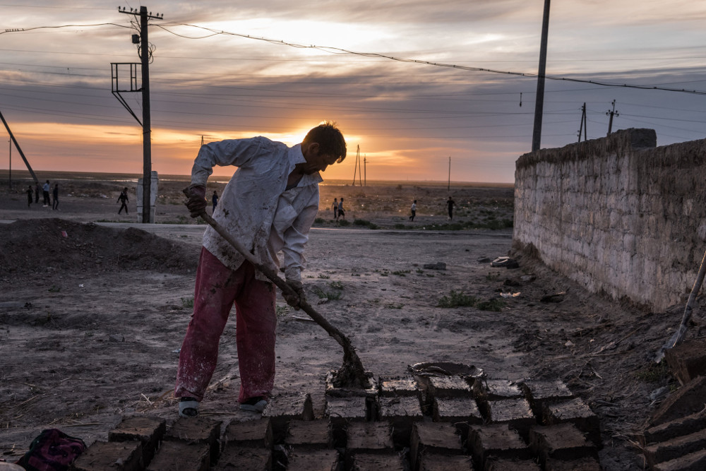 Making mud bricks to build a house in Muynak. Sergey Ponomarev for The New York Times