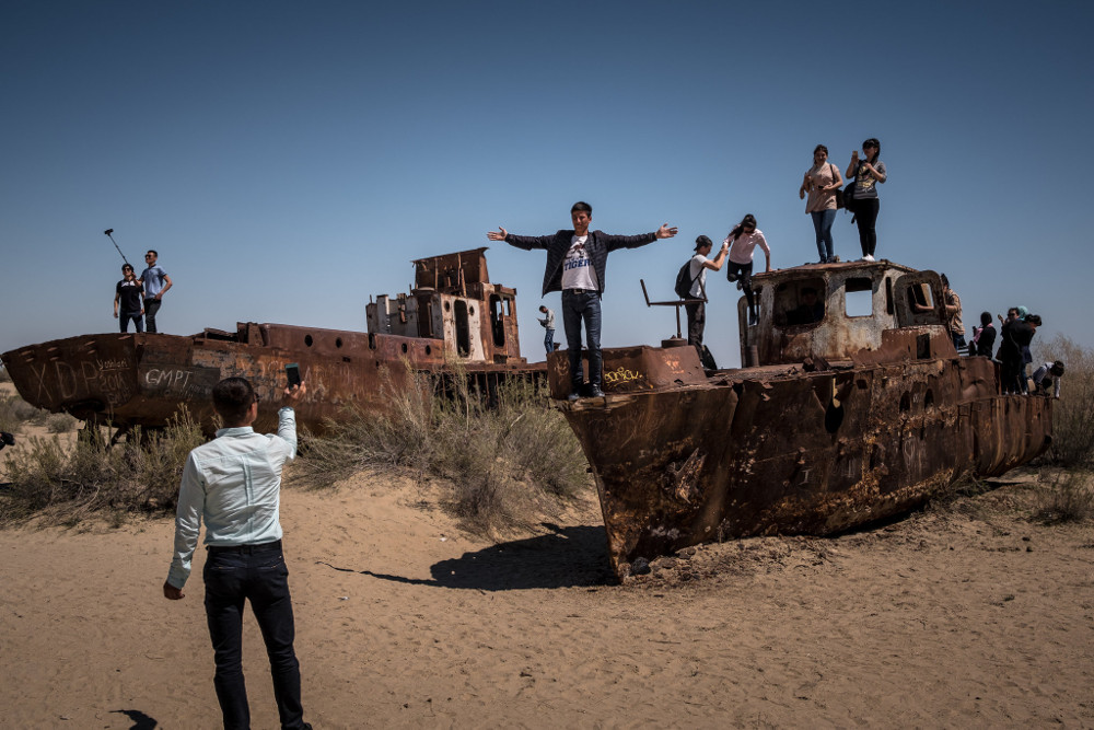 Tourists on stranded, rusted ships in Muynak. Sergey Ponomarev for The New York Times