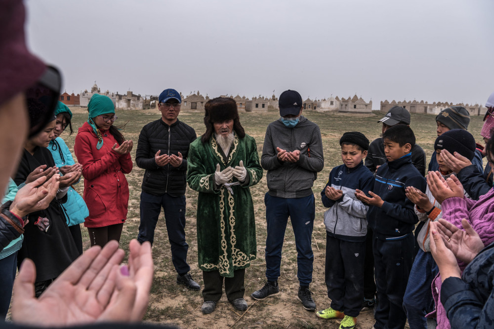 Karamalan, 82, an elder and herb healer, surrounded by locals at a cemetery in Amzin-Ata village, Kazakhstan. Sergey Ponomarev for The New York Times